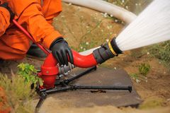 Fire hose in actions pouring water operated by fireman in orange Royalty Free Stock Photography