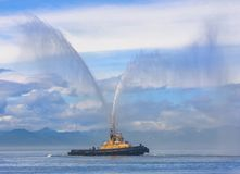 Fire hose boat spraying wate. R on Kamchatka on Paciic ocean Stock Image