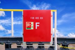 Fire hose box. Red hose boc on floating dock,extinguisher, hose and bucket on blue sky background Stock Image
