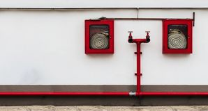 Fire hose cabinet on the white wall with many copy space Royalty Free Stock Photos