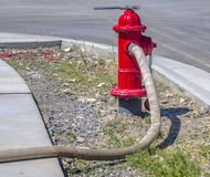 Fire hose conncted to hydrant. Red fire hydrant with hose connected for use in construction zone in Eagle Mountain, Utah royalty free stock images