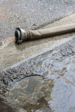 The fire hose with finnish coupler on wet road Royalty Free Stock Photography