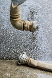 The fire hose with finnish coupler on wet road Royalty Free Stock Photo