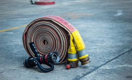 Fire-hose and nozzle on the ground. Fire-hose and nozzle on the rough ground stock photo