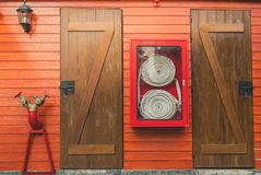Fire hose in red cabinet hanging on orange wooden wall. Fire emergency equipment box for safety and security system. Fire safety royalty free stock photography