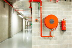 Fire hose reel. An fire hose hanging on the wall in an staircase royalty free stock photography