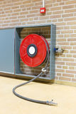 Fire hose on reel at wall. Red fire hose on reel hanging at wall Stock Image