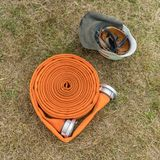 Fire hose and safety helmet. Top view  on an orange fire hose and safety helmet lie on the meadow Stock Photos