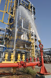 Fire hose spray water on fuel  refinery Stock Photo