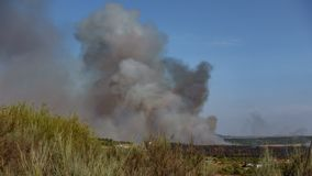 Fire with huge smoke near small village, time lapse stock video
