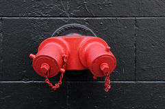 Fire Hydrant. Bright red fire hydrant on a stone wall Royalty Free Stock Images