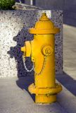 Yellow Fire Hydrant Stands on Concrete Downtown Royalty Free Stock Photo