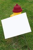 Fire Hydrant With Blank Sign. Bright colored fire hydrant with a blank sign ready for copy Royalty Free Stock Photos