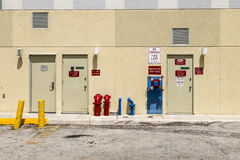 Fire hydrant and emergency exit at a backwards wall Stock Photo