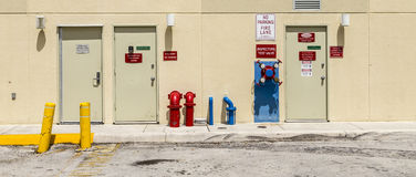 Fire hydrant and emergency exit at a backwards wall Stock Photography