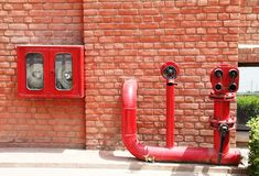 Fire hydrant,hose and pipes inserted on brick wall Stock Photo