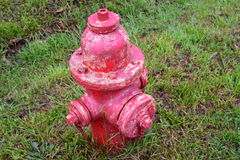 Fire hydrant needing a paint job. Red fire hydrant that is very much in need of a proper paint job stock images
