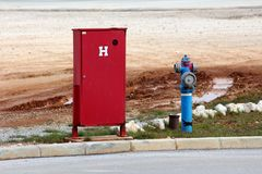 Fire hydrant next to fire department box. Metal blue fire hydrant with standard red fire department box next to local road with muddy tire tracks and gravel in stock images