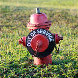 Fire Hydrant out-of-service. Fire Hydrant in a grassy field with out-of-service sign stock image