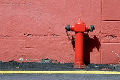 Fire hydrant. Red fire hydrant, Red connecting hydrant against the wall Stock Photo