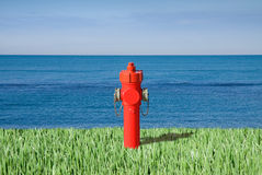 Fire hydrant by the sea. Plenty of water concept image Royalty Free Stock Image
