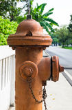 Fire hydrant. A side view of antique fire hydrant connection on the footpath with low concrete fence background stock image