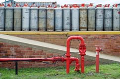 Fire hydrant water pipe in front of lpg gas bottles Royalty Free Stock Photos
