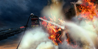 Fire intervention. Fireman, on the big ladder, switching off a big fire that burns part of a building Stock Photography