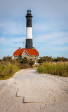 Fire Island lighthouse and house of lighthouse kee. Lighthouse keepers house in front of Fire Island lighthouse. A sand path leads from the beach to the Royalty Free Stock Images
