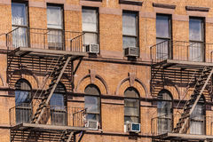 Fire ladder at old houses downtown in New York. Fire ladder at old red brick houses downtown in New York Royalty Free Stock Images