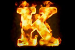 Fire letter K of burning flame light, 3D rendering. Isolated on black background Royalty Free Stock Photos