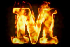 Fire letter M of burning flame light, 3D rendering. On black background Stock Photos
