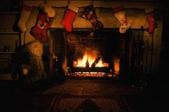 Fire-lit Stocking Hung Over Chimney. Stone and brick fireplace festooned with Christmas stockings and lighted by burning logs Royalty Free Stock Photography