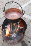Fire lit to boil water inside the large copper cauldron during h. Fire lit to boil water inside the large copper cauldron during medieval historical re-enactment stock photos