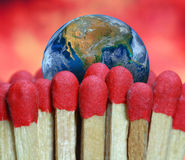 Fire match and the earth, including elements furnished by NASA Royalty Free Stock Images