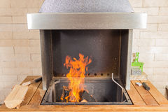 Fire in the modern bbq grill oven. Wood burning in the outdoor barbeque oven Royalty Free Stock Photography