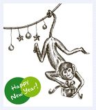 Fire Monkey Year. Monkey hanging on the garland and keeps Christmas gift Royalty Free Stock Images