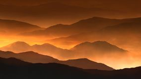 Fire mountain mist 4k loop. Features mountain ranges with a golden glow and mist flowing between the ranges in a loop stock footage