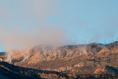 Fire in the mountains in the afternoon. Smoke over the mountains Royalty Free Stock Image