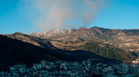Fire in the mountains in the afternoon. Smoke over the mountains Royalty Free Stock Images