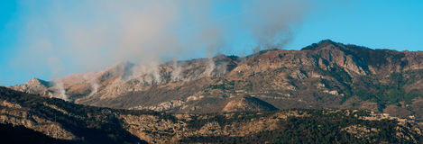 Fire in the mountains in the afternoon. Smoke over the mountains Stock Image
