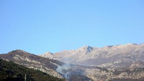 Fire in the mountains in the afternoon. Smoke over the mountains stock video footage