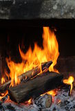 Fire in  old stone fireplace Stock Images
