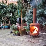 Fire oven in city garden. An oven with burning wood fire in a city garden in Amsterdam, The Netherlands stock image