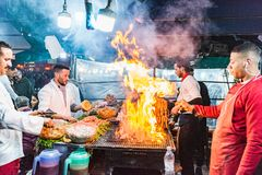 Fire over bbq grill at food stall in Morocco. Marrakech,Morocco - January 2018: Busy kitchen staff at open fire bbq at Jemma El Fna market square food stall stock images