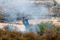 Fire in a Palestinian Field by Wall of Separation. Bil'in, Palestine - May 17th, 2013: A Palestinian person wearing a gas mask trying to put out fire caused by Stock Photos