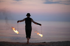 Fire performer back with burning poi on the beach Stock Image