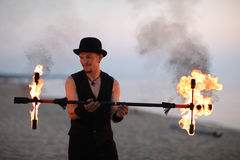 Fire performer with a fire baton Stock Photos