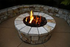 Fire pit. Stone fire pit on patio at dusk Stock Photography