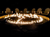 Fire pit Adirondack chairs. Inviting circle of fire and chairs makes darkness light and invites warmth and conversation Royalty Free Stock Photos